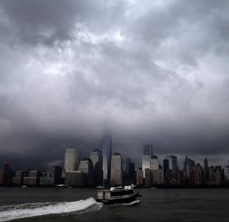 Image: A ferry leaves Jersey City, New Jersey as it heads across the Hudson River towards lower Manhattan and New York City as a heavy thunderstorm passes over the area