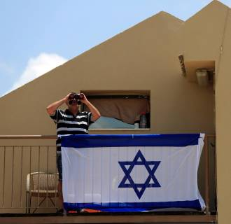 Image: A man watches towards the Gaza Strip from his balcony in the town of Sderot