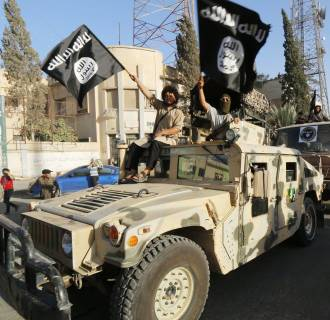 Image: Militant Islamist fighters take part in a military parade along the streets of Syria's northern Raqqa province