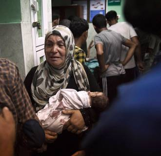 Image: A Palestinian woman holds an infant, whom medics said was injured in an Israeli shelling at a U.N-run school sheltering Palestinian refugees, at a hospital in the northern Gaza Strip
