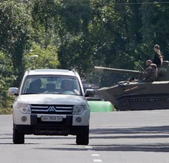 Image: Pro-Russian fighters ride a airborne self-propelled artillery gun Nona in downtown Donetsk, eastern Ukraine