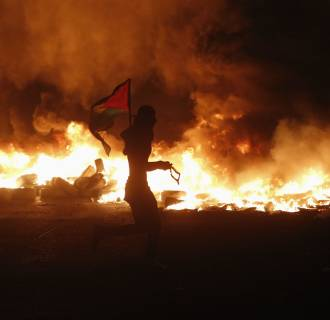 Image: Palestinian protester holds flag as he runs past burning tyres during clashes with Israeli troops, at Qalandia checkpoint