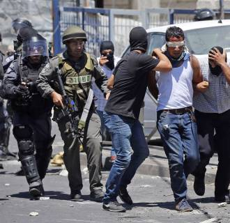 Image: Undercover Israeli policemen and uniformed policemen detain a Palestinian during clashes in the East Jerusalem neighbourhood of Wadi al-Joz during a protest against the Israeli offensive on Gaza