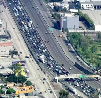Image: Police shut down both directions of the Golden State (5) Freeway in East LA on Friday, July 25, 2014, as authorities dealt with a man on the railing of a freeway overpass