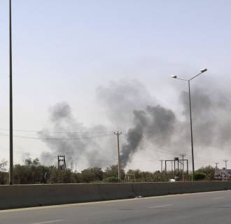 Image: Smoke rises over Airport Road area of Tripoli, after heavy fighting between rival militias broke out near the airport in Tripoli