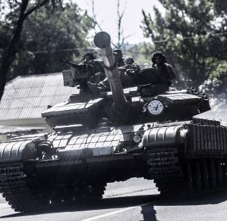 Image: Pro-Russian militants sit on a tank as they drive to the front line south of the city on July 27.