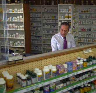 Image: A pharmacist stands behind the counter at a pharmacy in Vermont.
