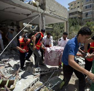Image: Palestinian medics carry the body of Jalila Ayad, a Christian woman found under the rubble of her home, after an Israeli airstike in Gaza City