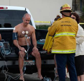 Image: A man is treated by a paramedics after a lightning strike in the water in Venice, Calif.