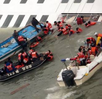 Image: South Korea Coast Guard members rescuing some of the passengers and crew aboard a ferry