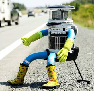 Image: The anthropomorphic robot named hitchBOT sits on the shoulder of Highway 102 to begin its 6000 kilometer cross country journey outside of Halifax