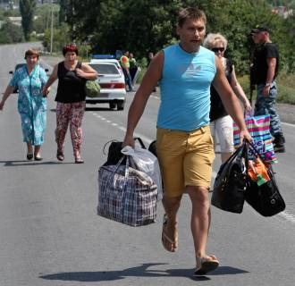 Image: Local residents carry their belongings as they flee from what they say was shelling by Ukrainian forces, in the town on the suburbs of Shakhtarsk