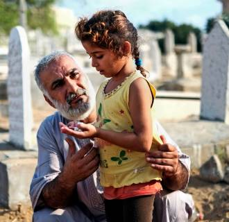 Image: A relative guides a girl in prayer at the grave of their loved one in a cemetery in Gaza city