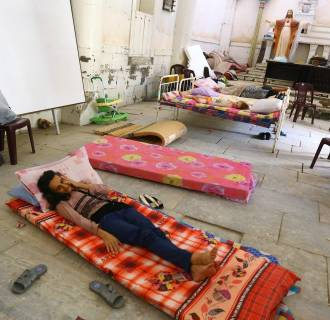 Image: An Iraqi Christian family fleeing the violence in the Iraqi city of Mosul, sleeps inside the Sacred Heart of Jesus Chaldean Church in Telkaif near Mosul, in the province of Nineveh