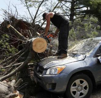 Image: A worker cuts a tree from on top of a storm-damaged car on Beach Street in Revere, Mass.