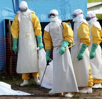 Image: Liberian health workers ready to load the body of a woman who died from the Ebola virus into a pickup