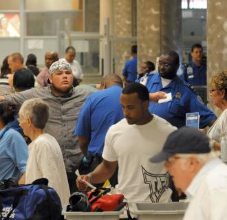 Image: Airline passengers go through the Transportation Security Administration security checkpoint at Hartsfield-Jackson Atlanta International Airport,