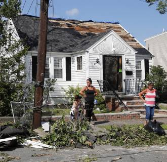 Image: Family members stand outside their damaged house in Revere, Mass.