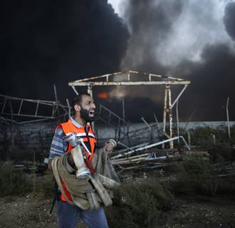 Image: Palestinian firefighter reacts as he tries to put out a fire at Gaza's main power plant in the central Gaza Strip