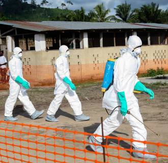 Image: Liberian health workers in protective gear on the way to bury a woman who died of the Ebola virus