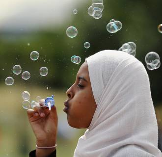 Image: A girl blows bubbles during an Eid celebration in Burgess Park