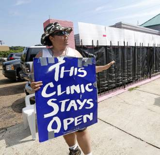 Image: Women protesters argue outside the Jackson Women's Health Organization clinic in Jackson, Miss., in 2013.