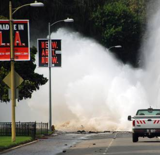 Image: Water shoots in the air from a broken 30-inch water main under Sunset Boulevard, uphill from UCLA