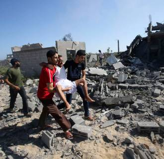 Image: Palestinians evacuate a man following what witnesses said was an Israeli air strike on a nearby house in Khan Younis in the southern Gaza Strip