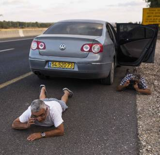 Image: Israelis take cover on the side of a road as a siren sounds warning of incoming rockets outside the northern Gaza Strip