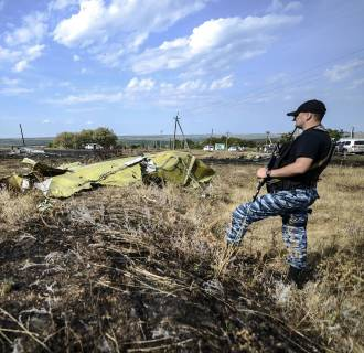 Image: A pro-Russian militant stands guard near a piece of debris at the crash site of the Malaysia Airlines Flight MH17