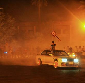 "Young Iraqi men gather to watch souped up cars intentionally spin out and skid: a dangerous sport called ""drifting."""