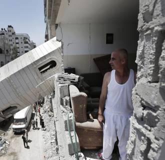 Image: Palestinian Ismail Radwan, 45, inspects the damage to his family apartment