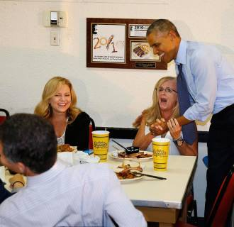 Image: U.S. President Barack Obama hugs an enthusiastic Dale Hopkins from Los Angeles as he visits Arthur Bryant's Barbeque restaurant in Kansas City