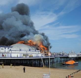 Image: Firefighters work to extinguish a fire on Eastbourne pier in Eastbourne, Britain