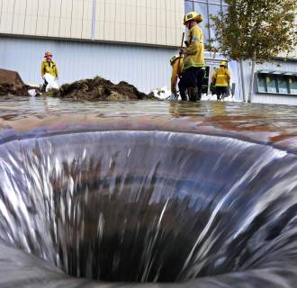 Image: Firefighters work near an open drain on the UCLA campus, which was flooded by a broken thirty inch water main in the Westwood section of Los Angeles