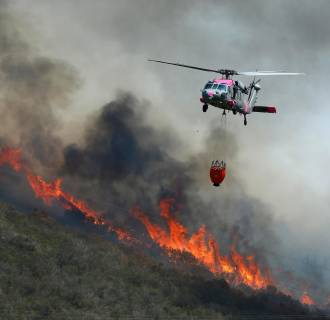 Image: A U.S. military helicopter makes a water drop on a hillside as fire fighters battle the Cocos Fire in San Marcos