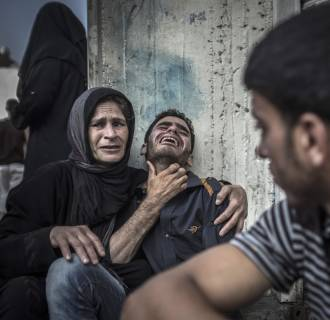 Image: Palestinians mourn the death of a relative, who died when a UN school used as a shelter for internally displace people came under Israeli shelling