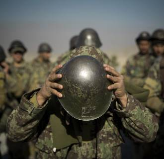 Image: An Afghan army soldier adjusts his helmet as he lines up with others at a training facility in the outskirts of Kabul, Afghanistan.