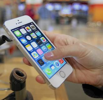 Image: A customer examines a new iPhone 5s