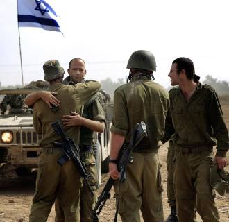 Image: Israeli reserve soldiers greet each other after a few weeks apart near the Israel-Gaza border.