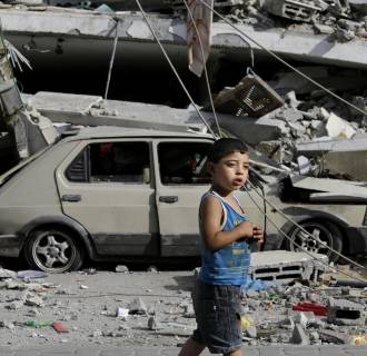 Image: Palestinian Abdel Aziz Jendiyah, 4, walks past a six-story building, destroyed by an Israeli strike earlier during the war