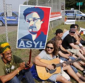 Image: A demonstrator against spying holds a sign asking for asylum for former NSA contractor Edward Snowden