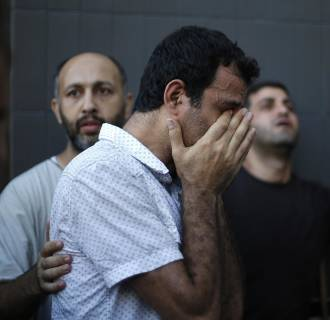 Image: A relative of Palestinians whom medics said were killed in an Israeli air strike on their van grieves at a hospital in Gaza City