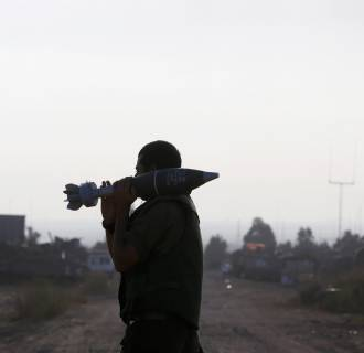 Image: An Israeli soldier carries a 120 mm mortar shell outside the central Gaza Strip