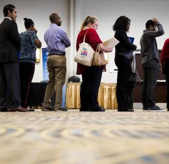 Job seekers wait in line to meet with recruiters during a job fair in Philadelphia.