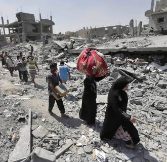 Image: Palestinians carry their belongings after salvaging them from their destroyed houses in the heavily bombed town of Beit Hanoun, Gaza Strip, close to the Israeli border,