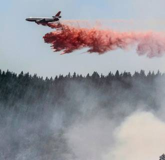 Image: A plane drops fire retardant as firefighters battle a blaze in El Portal, Calif., near Yosemite National Park