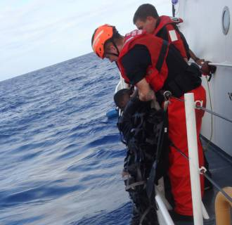 Image: A Haitian minor is rescued by the crew of the Coast Guard cutter Key Largo