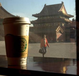 Image: A tourist walks past the windows to an outlet of Starbucks at the Forbidden City in Beijing, China