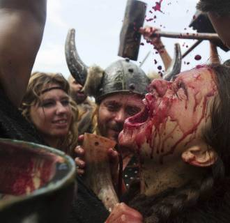 Image: A woman dressed up as a Viking drinks local red wine during the annual Viking festival of Catoira in north-western Spain